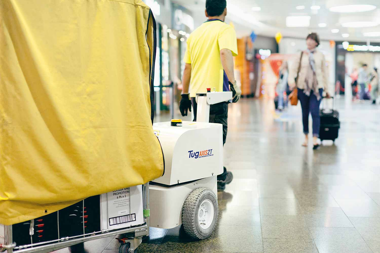 Electrodrive's Tug Axis towing a large trolley through an airport